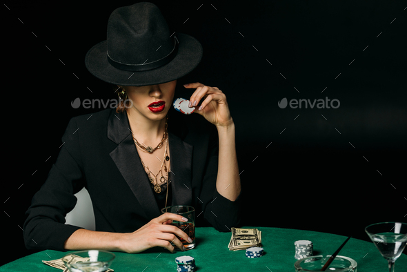attractive girl in jacket and hat holding glass of whiskey and poker chips at table in casino - Stock Photo - Images