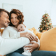 happy man embracing wife with sitting on sofa and holding cute baby - PhotoDune Item for Sale