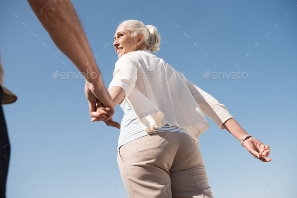 Cropped shot of smiling senior woman holding hand of senior man and walking outdoors - Stock Photo - Images