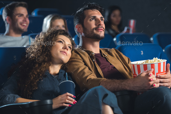 young couple with popcorn holding hands while watching movie together in cinema - Stock Photo - Images