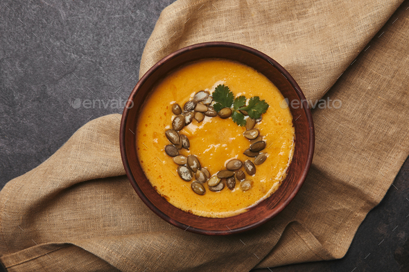 top view of tasty healthy pumpkin soup with seeds in bowl on sackcloth - Stock Photo - Images