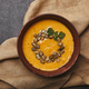 top view of tasty healthy pumpkin soup with seeds in bowl on sackcloth - PhotoDune Item for Sale