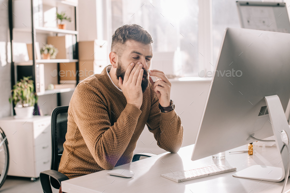 sick businessman sitting at office desk with runny using nasal spray - Stock Photo - Images