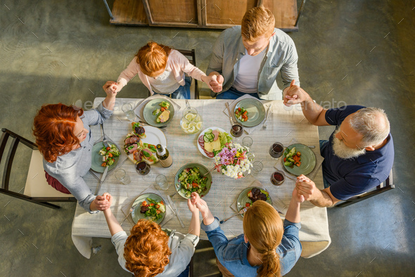 overhead view of family holding hands and praying while having dinner together - Stock Photo - Images