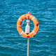 Lifebuoy orange on vertical iron against blue sea background. - PhotoDune Item for Sale