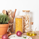 Assortment of pasta in glass jars, olive oil, vegetables and kitchen utensils on wooden table - PhotoDune Item for Sale