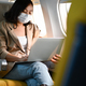 Woman wearing mask is using her laptop during an airplane flight. - PhotoDune Item for Sale