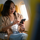 Young women use smartphones during plane travel. - PhotoDune Item for Sale