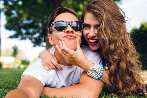 Selfie-portrait of funny couple lying on grass in summer park. Girl with long curly hair, red lips a - Stock Photo - Images
