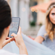 Portrait from back brunette girl taking photo on phone of pretty blonde woman on street - PhotoDune Item for Sale