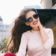 Closeup portrait of attractive girl in sunglasses with vinous lips in the city. Her long hair is fly - PhotoDune Item for Sale