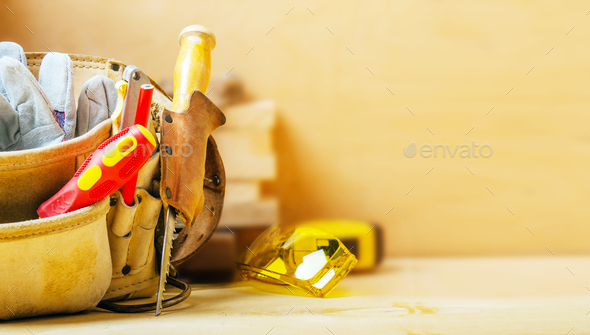 Closeup view at tool belt with carpenter tools and protective glasses. Space for text - Stock Photo - Images