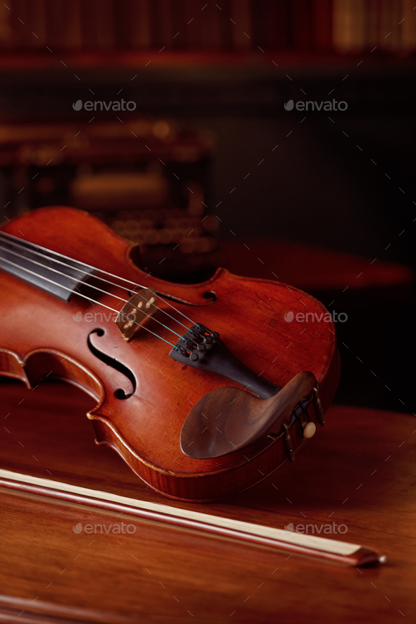 Violin in retro style and bow on wooden table - Stock Photo - Images
