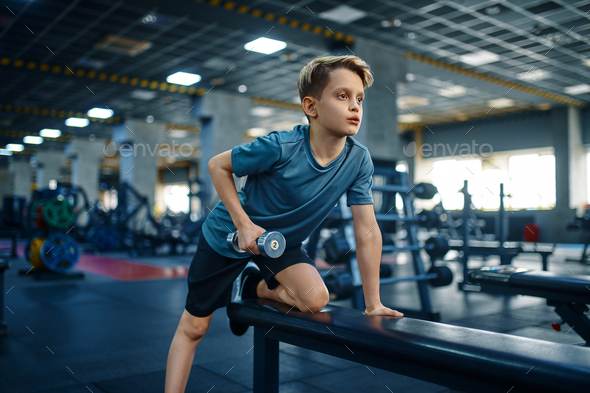 Youngster doing exercise with dumbbell on bench - Stock Photo - Images