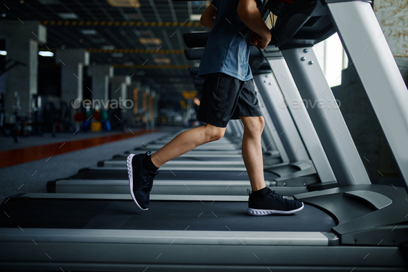 Youngster doing exercise on treadmill in gym - Stock Photo - Images