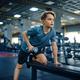 Youngster doing exercise with dumbbell on bench - PhotoDune Item for Sale