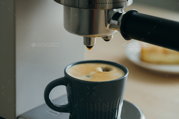 Morning ritual at breakfast with pouring coffee from coffee machine, drops of espresso dripping - Stock Photo - Images