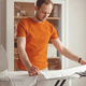 Young man ironing children's sheet on ironing board at home - PhotoDune Item for Sale