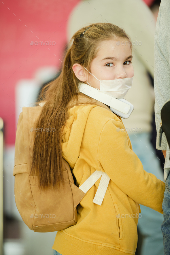Cute little traveler with backpack turning her head back while looking at you from queue - Stock Photo - Images