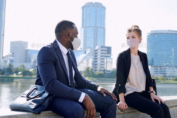 Two young intercultural business partners in formalwear and protective masks interacting at meeting - Stock Photo - Images