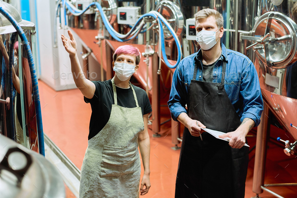 Two young brewers in protective masks discussing quality of new beer production equipment - Stock Photo - Images