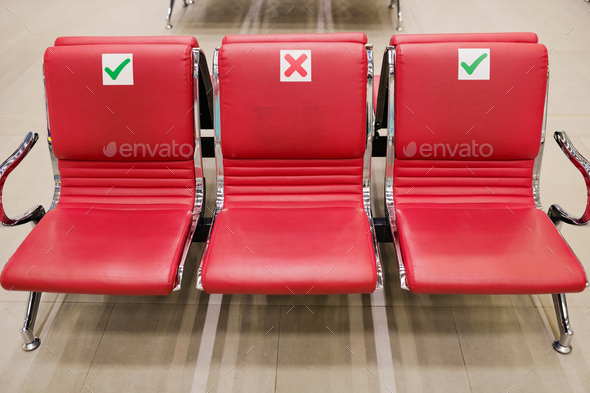 Row of three empty red leather seats inside lounge of large contemporary airport where you can relax - Stock Photo - Images
