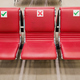Row of three empty red leather seats inside lounge of large contemporary airport where you can relax - PhotoDune Item for Sale