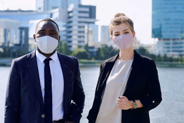 Two young intercultural managers in formalwear and protective masks standing against cityscape - Stock Photo - Images
