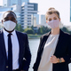 Two young intercultural managers in formalwear and protective masks standing against cityscape - PhotoDune Item for Sale