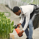 African guy works in garden and waters flowers - PhotoDune Item for Sale