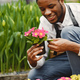 Gardener inspects flowers in a pot in greenhouse - PhotoDune Item for Sale