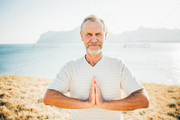 Close up portrait senior man doing yoga exercises at the mountain on the background. - Stock Photo - Images