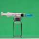 Syringe on top on a vaccine bottle, green background. - PhotoDune Item for Sale