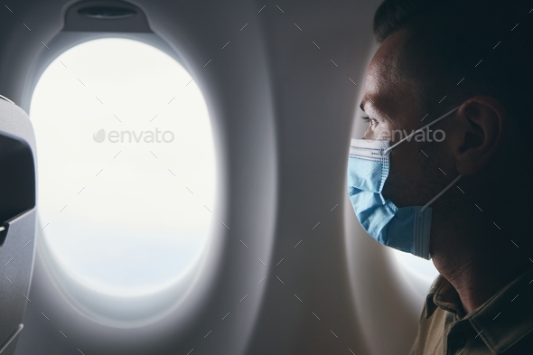 Man wearing face mask inside airplane during flight - Stock Photo - Images