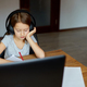 Cute little girl with headphones using laptop to study at home - PhotoDune Item for Sale