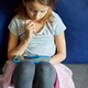 Cute little girl sitting on couch, playing online game on digital tablet computer - PhotoDune Item for Sale