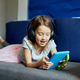 Cute little girl lying on couch, playing online game on digital tablet computer - PhotoDune Item for Sale