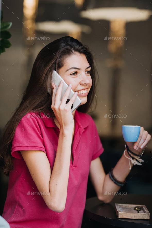 Slender slim brunette girl talking on the cell phone in cafe. Body health, slimness, self-love - Stock Photo - Images