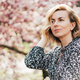 Beautiful woman in her forties. Profile portrait with a pink flowering magnolia tree as background. - PhotoDune Item for Sale