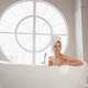 Young woman relaxing lying in bathtube in luxury bathroom with round large window - PhotoDune Item for Sale