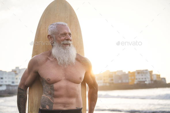 Tattooed senior surfer holding vintage surf board on the beach at sunset - Stock Photo - Images