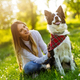 Happy young woman playing with her dog in park - PhotoDune Item for Sale