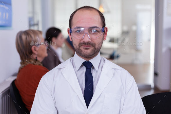 Portrait of stomatologist smiling at camera being in dental office - Stock Photo - Images