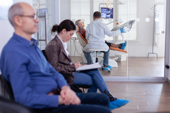 Senior woman sitting on chair in dental office listening dentist - Stock Photo - Images