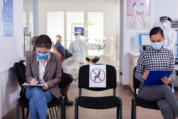Patient with face protection mask writing on registration form - Stock Photo - Images