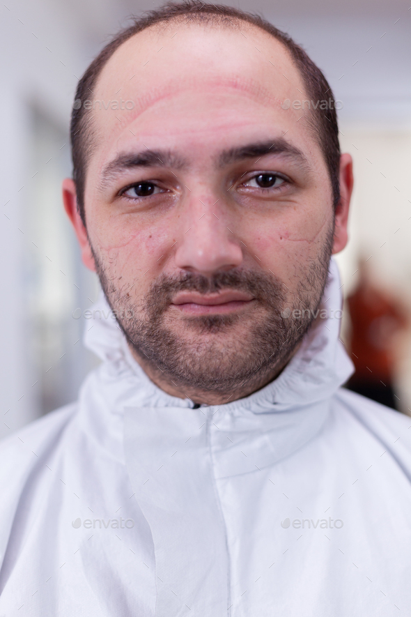 Close up portrait of tired doctor wearing safety protection suit - Stock Photo - Images