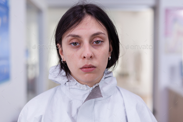 Close up of exhausted nurse in office looking on camera wearing ppe suit - Stock Photo - Images