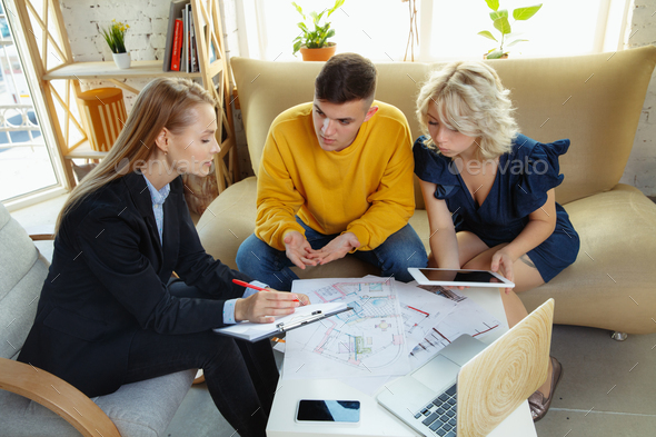 Interior designer working with young couple. Lovely family and professional designer or architector - Stock Photo - Images