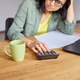 Stylish brunette woman in glasses sitting at wooden table with notepad working in her office - PhotoDune Item for Sale