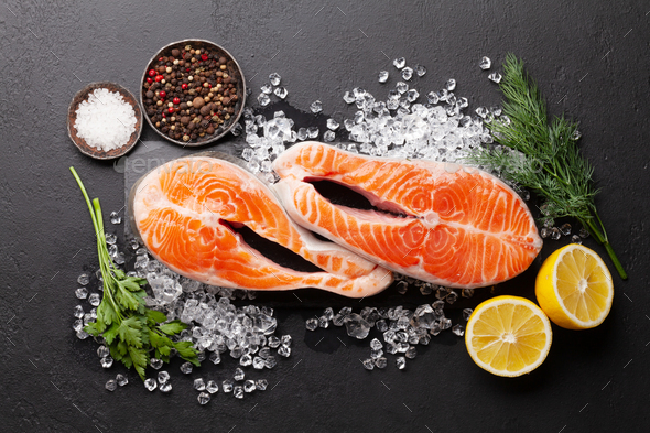 Fresh raw salmon cooking. Fish steaks with herbs and spices - Stock Photo - Images